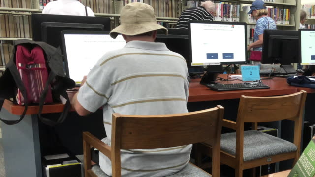 seniors reading and using computer at library - e learning stock videos and b-roll footage