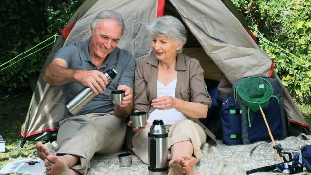 WS Seniors sitting and drinking coffee in front of tent in Park / Cape Town, Western Cape, South Africa