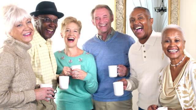 Seniors socializing, talking over coffee