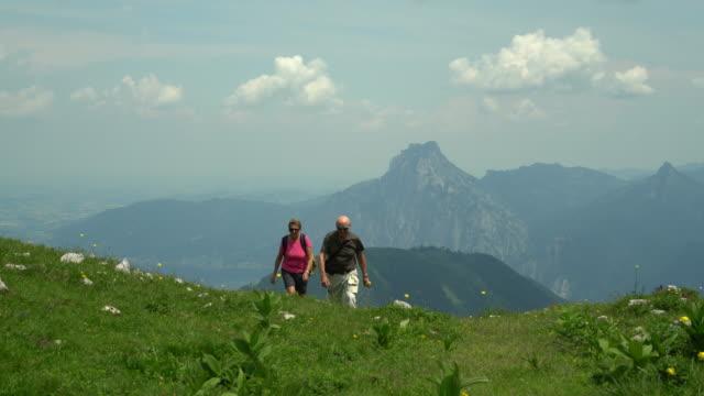 Seniors Taking on the World, active senior couple walking up mountain pasture