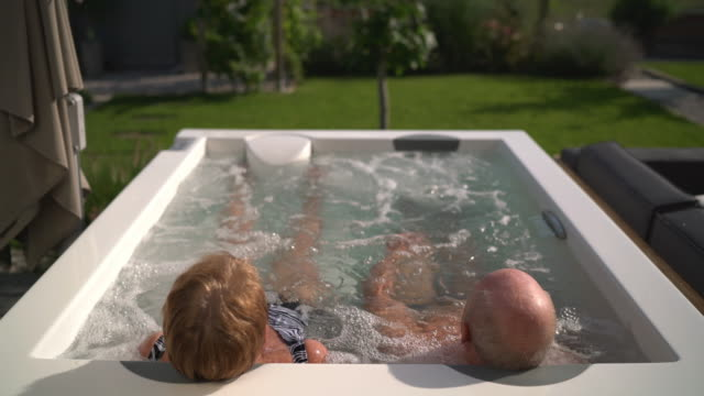seniors taking on the world, couple in hot tub in garden - hot tub stock videos & royalty-free footage