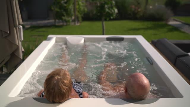 vídeos de stock, filmes e b-roll de seniors taking on the world, couple in hot tub in garden - banho terapêutico