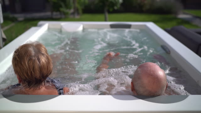 seniors taking on the world, senior couple relaxing in whirlpool outdoors - balding stock videos and b-roll footage