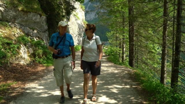 vidéos et rushes de seniors taking on the world, senior tourist couple on hiking vacations - short