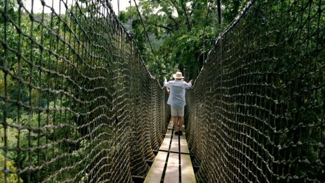 vídeos de stock e filmes b-roll de seniors taking on the world - ponte suspensa
