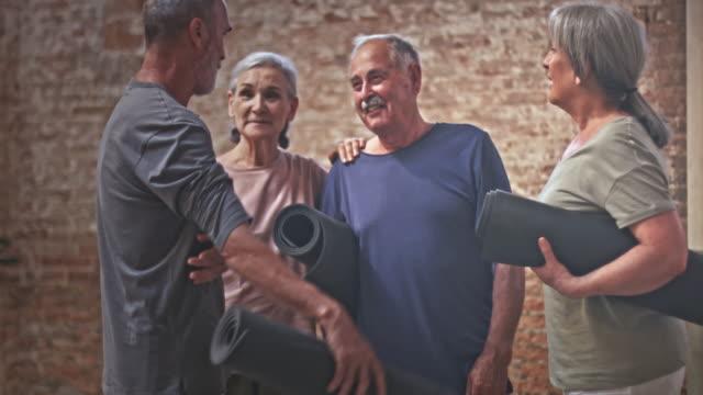 Seniors talking in yoga studio
