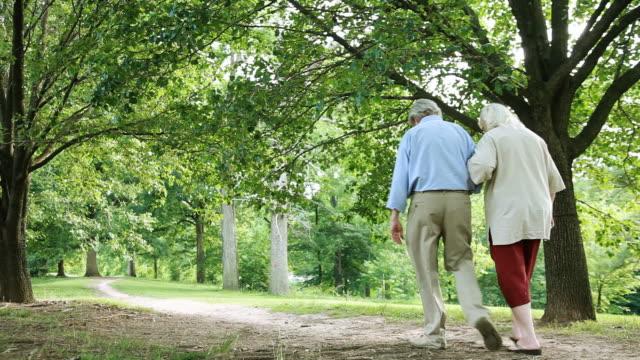 vídeos de stock, filmes e b-roll de idosos caminhada no parque - de braços dados