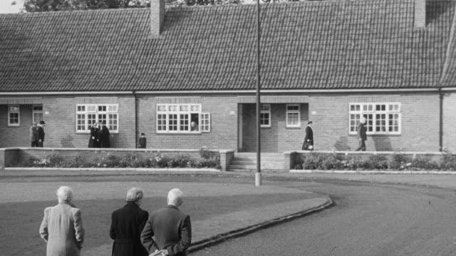 vídeos y material grabado en eventos de stock de 1951 montage seniors walking in their bungalow community and playing cards / united kingdom - 1951