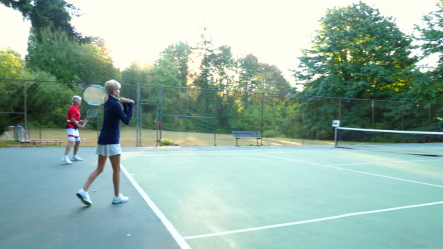 vidéos et rushes de pan seniors warming up for mixed doubles tennis match - petit groupe de personnes