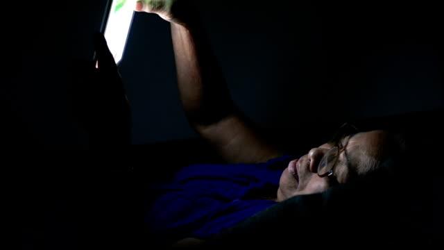 Seniors woman using tablet pc at night
