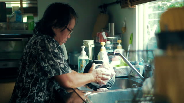 seniors woman washing dishes at home - washing up stock videos and b-roll footage