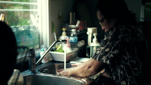 seniors woman washing dishes at home - stained clothes stock videos and b-roll footage
