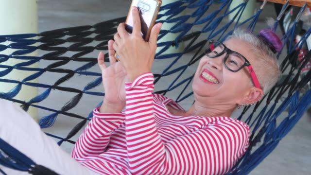 senoir frau verwenden smartphone auf krippe - serene people stock-videos und b-roll-filmmaterial