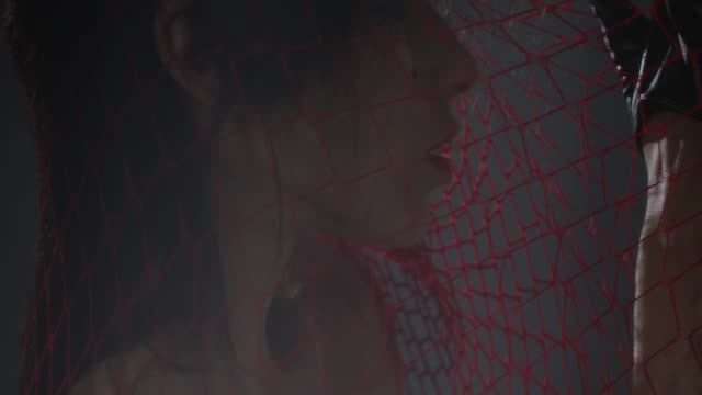 sensual brunette fashion model trapped in a red netting shows facial expressions. fashion video. - lip liner stock videos & royalty-free footage