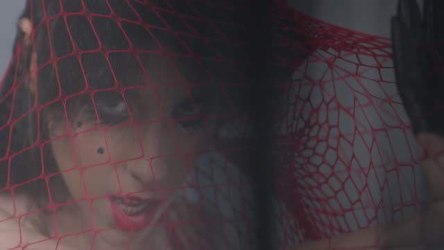 sensual brunette fashion model trapped in a red netting shows facial expressions. fashion video. - haute couture stock videos and b-roll footage