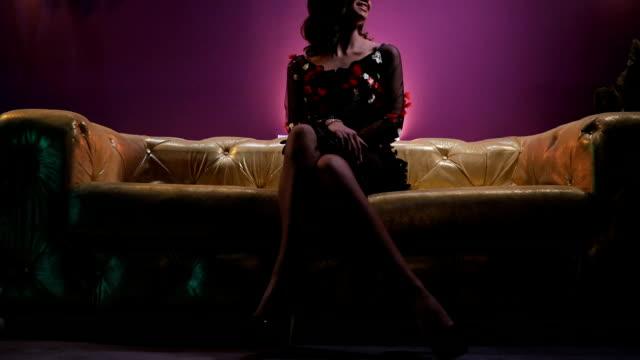 vídeos de stock, filmes e b-roll de moça morena sensual, sentada no sofá colorido ouro - de pernas cruzadas