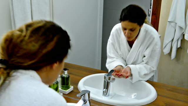 Sensual woman in bathrobe washing her face in bathroom