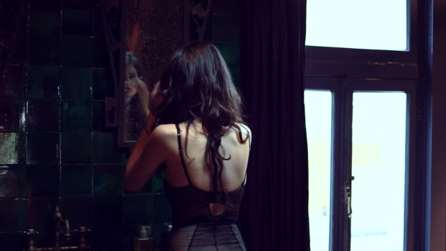 MS Sensuous young woman standing in front of mirror and adjusting hair