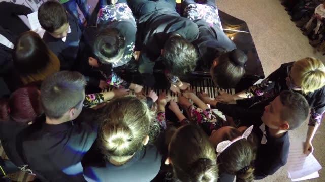 sentados o de rodillas parados o acostados sobre el piano 18 adolescentes bosnios y sus dos profesores de musica tocaron juntos un mismo piano con la... - afp stock videos & royalty-free footage