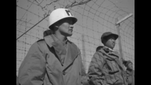 stockvideo's en b-roll-footage met sentry in tower overlooking scores of tents / vs line of communist prisoners of war under guard stretches to the horizon / mp with quonset hut behind... - mp