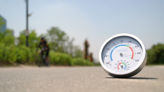 vidéos et rushes de seoul citizen riding a bike in han river park's cycle path during summer heat wave - macadam