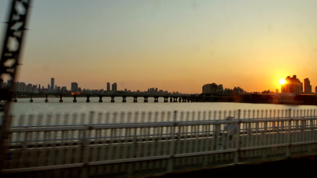 seoul subway train crossing han river at sunset - zugperspektive stock-videos und b-roll-filmmaterial