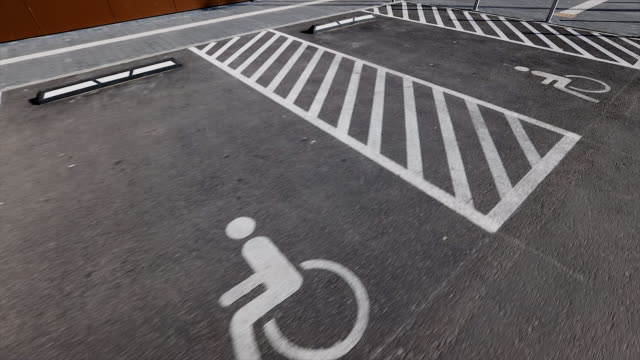 separated disabled signs on asphalt parking lots near shopping centre or mall - disability icon stock videos & royalty-free footage