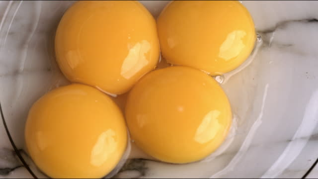 separated egg yolks being added to glass mixing bowl for flourless chocolate cake recipe - egg yolk stock videos & royalty-free footage