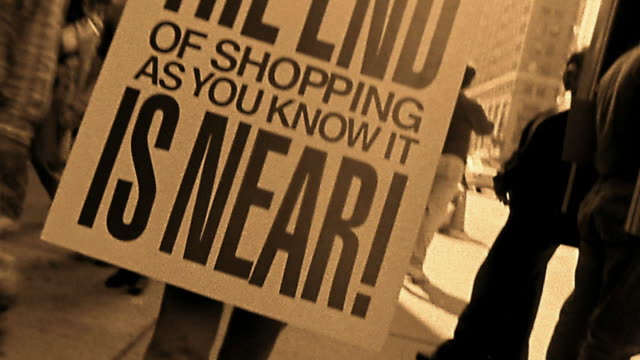 Sepia low angle close up man in sandwich board sign: 'End (of shopping) is Near' walking down crowded sidewalk