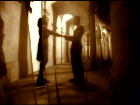 sepia tone pan ws unidentifiable female male couple standing in coliseum style corridor behind see through curtain embracing amour love lovers... - sepia stock videos and b-roll footage