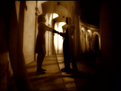 sepia tone: unidentifiable female & male couple standing in coliseum style corridor behind see through curtain embracing. amour, love, lovers,... - sepia stock videos & royalty-free footage