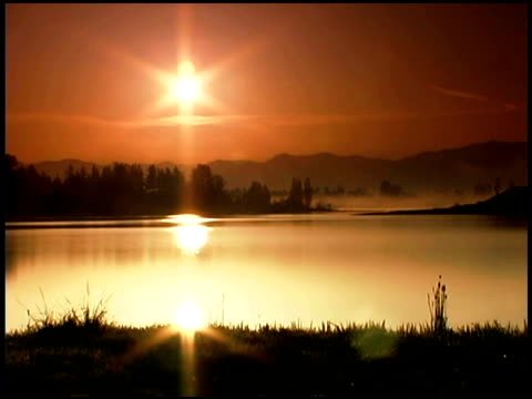 a sepia toned scenic of the sun setting over the mountains near lake tapps, wa. - sepia stock videos and b-roll footage