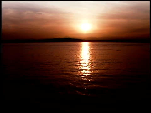 sepia wide shot of the sun setting over the mountains surrounding the puget sound. - sepia stock videos and b-roll footage