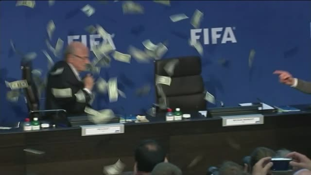 sepp blatter suspended from fifa lib / tx blatter at press conference as interrupted by comedian lee nelson who showers fake dollar bills over the... - simon brodkin comedian stock videos and b-roll footage