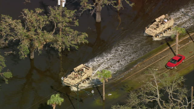 sept 11 2005 aerial apcs driving on flooded street in aftermath of hurricane katrina / new orleans - 救う点の映像素材/bロール