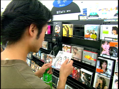 september 1, 2005 man shopping for cds at a department store / china - 2000s style stock videos & royalty-free footage