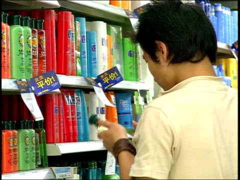 vidéos et rushes de september 1, 2005 man shopping for shampoo at a department store / china - style des années 2000