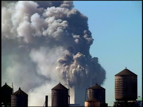 vidéos et rushes de september 11 2001 wide shot wtc tower burning / north tower collapsing / water towers in foreground / nyc - terrorisme