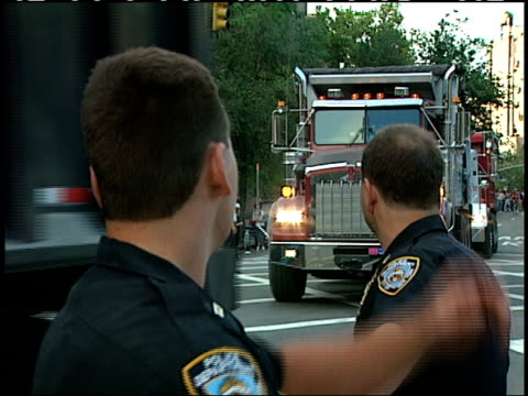 september, 12 2001 panning two police officers directing dump trucks down the street passing pedestrians / new york city, new york, united states - 2001 stock videos & royalty-free footage