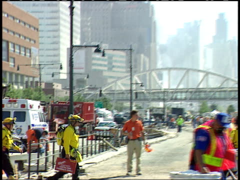 September 13 2001 ZO Firefighters and rescue personnel carrying equipment toward vehicles with the altered Manhattan skyline behind / New York City...