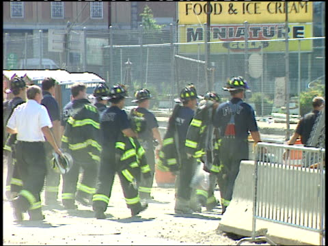 september 13, 2001 firefighters walking through dust and debris covered city street past concrete barricades after the terrorist attack / new york... - 2000s style stock videos & royalty-free footage