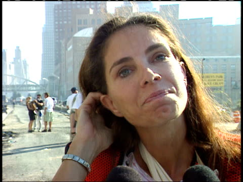 vídeos de stock e filmes b-roll de september 13, 2001 volunteer worker holding gas mask and giving interview regarding rescue effort of word trade center disaster amidst backdrop of... - pessoas ao fundo