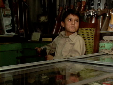 stockvideo's en b-roll-footage met september 15 2005 ms zi cu boy playing with pistol in gun shop / peshawar pakistan / audio - vuurwapenwinkel