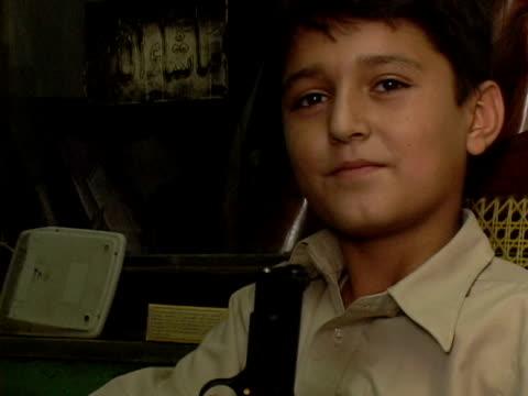 september 15 2005 cu zo ms boy playing with pistol in gun shop / peshawar pakistan / audio - gun shop stock videos & royalty-free footage