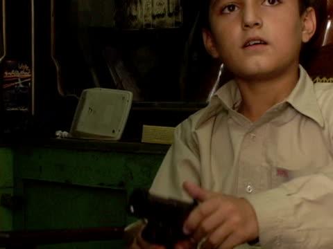september 15 2005 ms boy playing with pistol in gun shop / peshawar pakistan / audio - gun shop stock videos & royalty-free footage