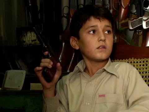 september 15 2005 ms zi cu boy playing with pistol in gun shop / peshawar pakistan / audio - gun shop stock videos & royalty-free footage
