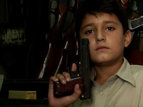 stockvideo's en b-roll-footage met september 15 2005 cu zo ms boy playing with pistol in gun shop / peshawar pakistan / audio - vuurwapenwinkel