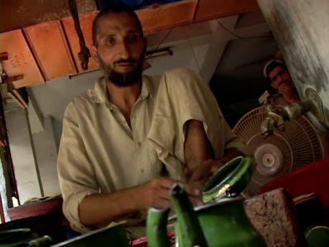 vídeos de stock e filmes b-roll de september 15, 2005 man preparing and selling tea / peshawar, pakistan / audio - só homens de idade mediana