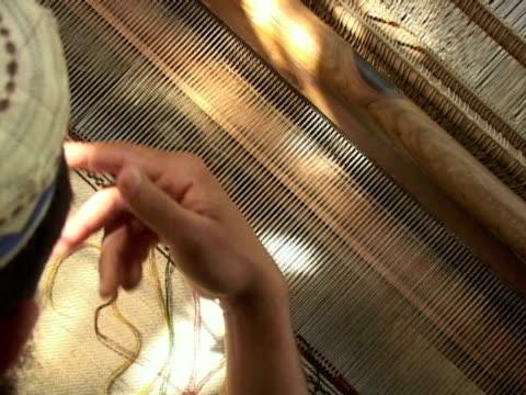 vidéos et rushes de september 15, 2005 man weaving carpet in sewing press machine / peshawar, pakistan / audio - un seul homme d'âge moyen