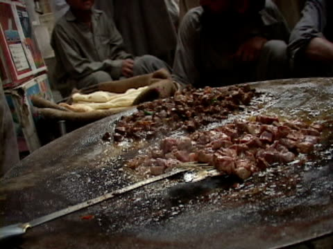 september 15, 2005 vendor cooking food for sale at stand, people observing / peshawar, pakistan / audio - peshawar stock videos & royalty-free footage